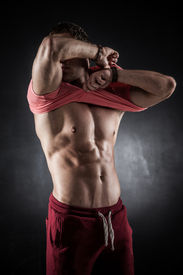 pic of lifting-off  - Brutal athletic man taking shirt off on gray background - JPG