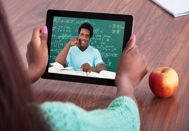 foto of teachers  - Cropped image of female teacher assisting student through video conferencing at classroom - JPG