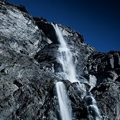 Waterfall in high mountains in Pyrenees. Dark contrast twilight colors.