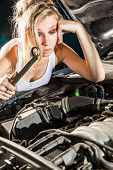 Puzzled Girl Trying To Repair Their Own Broken Car