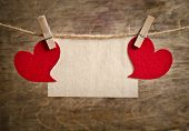 Two Red Fabric Hearts With Sheet Of Paper Hanging On The Clothesline On Two Clothespins . On Old Woo