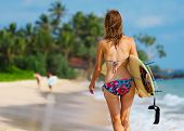stock photo of board-walk  - Young lady walking with surf board on sandy tropical beach - JPG