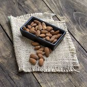 Almonds In  Bowl On Grained Wood Background