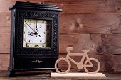 Retro clock with decorative bicycle on table on wooden background
