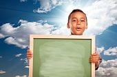 Proud Hispanic Boy Holding Blank Chalkboard Over Sky