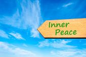 image of peace-sign  - Wood arrow sign against clear blue sky with Inner Peace message - JPG