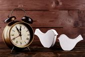 Retro clock with decorative birds on table on wooden background