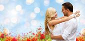 summer holidays, people, love and dating concept - happy couple hugging over blue sky lights and poppy field background