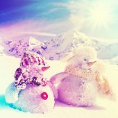 Winter, snow, sun and fun, winter vacation, Christmas - happy snowman friends and snowy mountains in background, filtered