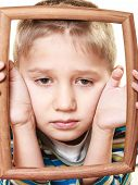 picture of sad boy  - Portrait of little sad blonde boy child holding photo frame framing his face looking up studio shot isolated on white - JPG