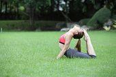 Young Woman Practicing Yoga, Eka Pada Rajakapotasana (king Pigeon Pose) Pose On Lawn