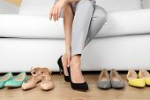 Trying on shoes by elegant lady sitting on white sofa background