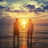 Silhouette of a young couple on their honeymoon standing on the ocean beach at amazing sunset.