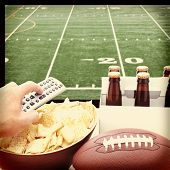 Closeup of a man's hand holding a TV remote with a bowl of chips and a six pack of beer with a football field on the television screen in the background. Square Format with instagram effect applied.
