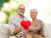 family, holidays, age and people concept - happy senior couple holding little red paper heart shape cutout and sitting on sofa over green background