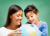 children, education, geography, school and happy people concept - happy teacher and girl with globe over green chalk board background