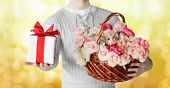 holidays, people, feelings and greetings concept - close up of man holding basket full of flowers and gift box over yellow lights background