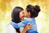 family, children and happy people concept - happy little girl hugging and kissing her mother over yellow lights background