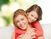 people, love, holidays, family and motherhood concept - happy mother and daughter hugging over green background