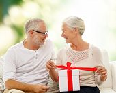 family, holidays, age and people concept - happy senior couple with gift box over green background