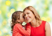 people, trust, love, family and motherhood concept - happy daughter whispering gossip to her mother over green lights background