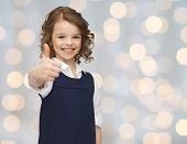people, gesture, children, summer vacation and happiness concept happy little school girl showing thumbs up over holidays lights background