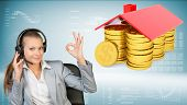 Businesswoman in office chair making okay gesture. Piles of golden dollars under roof beside