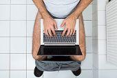 Man In Toilet Using Laptop