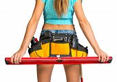 Woman wearing tool belt with tools holding builders level, close up