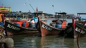 PULAU KETAM, MALAYSIA - JANUARY 18, 2015: Traditional Malay fishing boats dock side by side at the fisherman's wharf after return from sea. This island is famous for sea food products and restaurants.