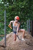 Pretty Young Woman Builder Digging A Shovel