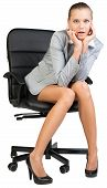 Businesswoman on office chair, looking surprised or astonished