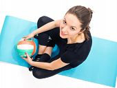 Fit woman with volley ball sitting on exercise mat
