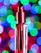 Women's perfume in beautiful bottle on festive shiny background