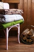 Warm plaids on chair on rustic wooden background