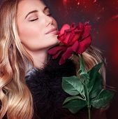 Closeup portrait of beautiful blond woman with closed eyes smelling fresh rose on dark red background, enjoying romantic holiday, happy Valentine day concept