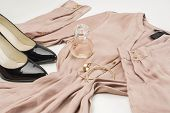 picture of perfume  - Elegant ladies fashion ensemble with a stylish dress classic patent leather black court shoes gold bangles and bottle of perfume or scent laid out ready to wear on a white background low angle - JPG