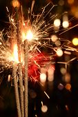 Three burning christmas sparklers.