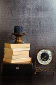 Vintage clock and books on dark background