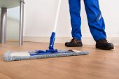stock photo of janitor  - Low Section Of A Janitor Mopping Floor