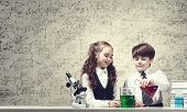 Cute girl and boy at chemistry lesson making tests