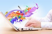 Close up of man's hands using laptop and splashes out of monitor