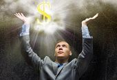 Businessman praying at dollar sign above