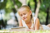 Little cute girl in summer park on blanket with tablet pc