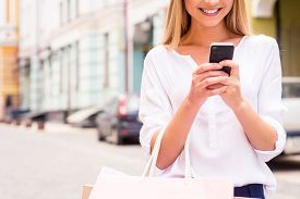 image of adults only  - Close-up of beautiful young smiling woman holding shopping bags and mobile phone while standing outdoors ** Note: Shallow depth of field - JPG