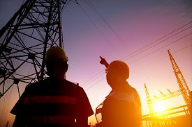 picture of substation  - two worker watching the power tower and substation with sunset background - JPG