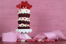 stock photo of red velvet cake  - Novelty triple layer red velvet cupcake on white cake stand with ribbons and candy against a vintage shabby chic pink and red wood background - JPG