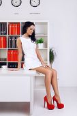 stock photo of provocative  - sexy provocative businesswoman at office sitting on table - JPG