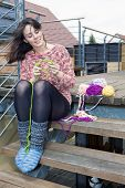 stock photo of knitting  - young woman sitting outdoors and is knitting - JPG