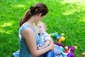 stock photo of breastfeeding  - Mother woman breastfeeding baby boy kid on background of grass in park - JPG
